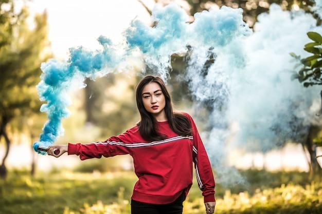 Junge asiatische frau, die blaue bunte rauchbombe auf dem außenpark hält. blauer rauch breitet sich aus