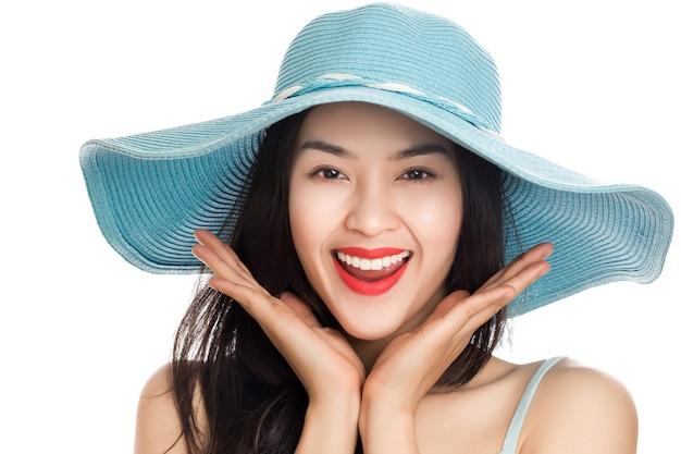 Junge asiatische frau, die blauen strohhut mit ausdruck der überraschung lokalisiert auf weiß trägt.