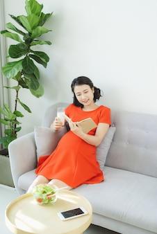 Junge asiatische frau, die buch liest, das am sofa entspannt und milch trinkt.