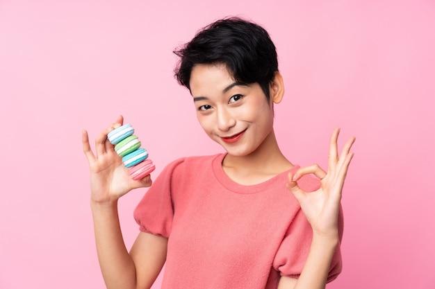 Junge asiatische frau, die bunte französische macarons hält und ok zeichen mit den fingern zeigt