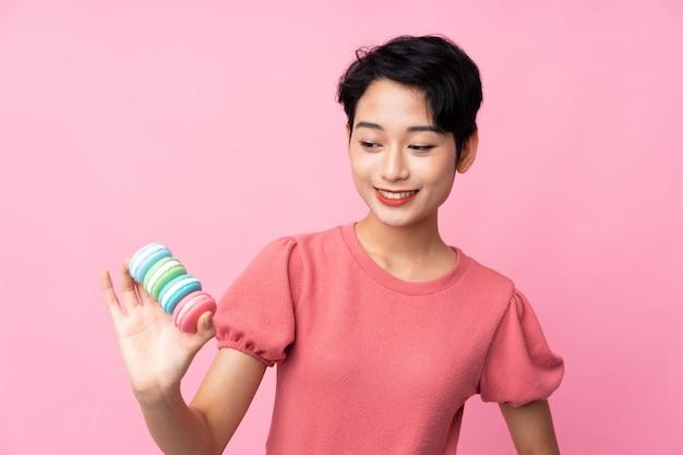 Junge asiatische frau, die bunte französische macarons und glücklich hält