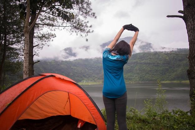 Junge asiatische frau, die camping oder picknick im waldsee kampiert.
