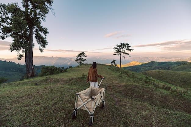 Junge asiatische frau, die campingwagen auf grünem hügel in der landschaft bei sonnenuntergang schleppt