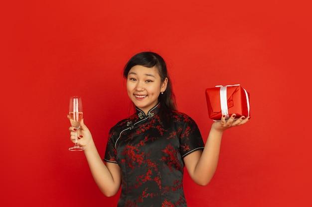 Junge asiatische frau, die champagner trinkt und geschenk hält