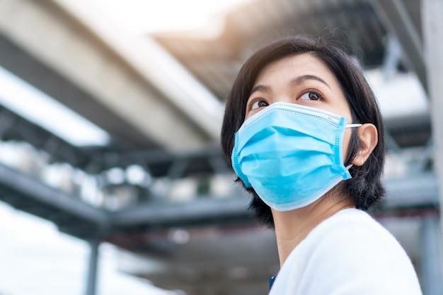Junge asiatische frau, die chirurgische maske im neuen normalen leben im freien trägt