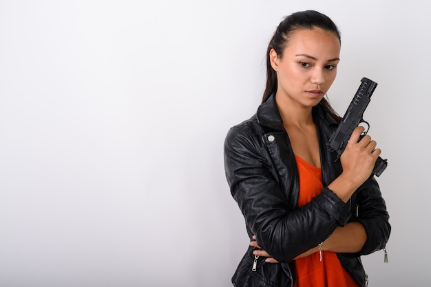 Junge asiatische frau, die denkt, während sie unten schaut und pistole gegen leerraum hält
