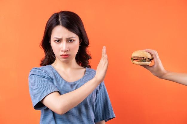 Junge asiatische frau, die die gewohnheit aufgibt, hamburger zu essen