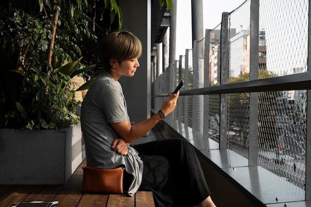 Junge asiatische frau, die draußen ihr smartphone überprüft
