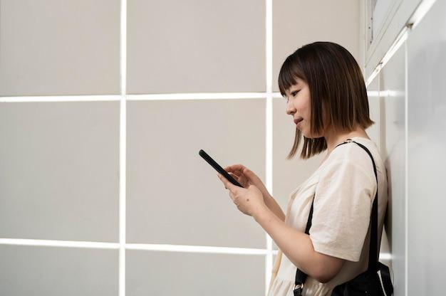 Junge asiatische frau, die draußen ihr telefon überprüft