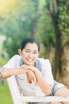 Junge asiatische frau, die draußen sich entspannt und glücklich lächelt