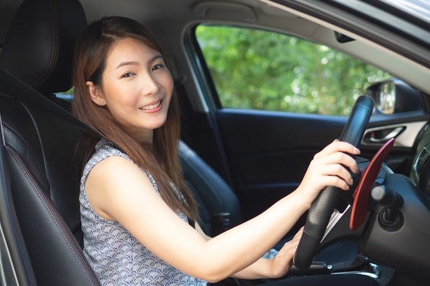 Junge asiatische frau, die ein auto antreibt