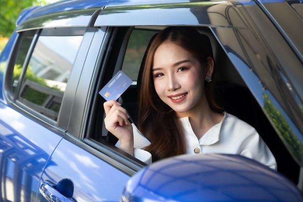 Junge asiatische frau, die ein auto fährt und kreditkarte hält.