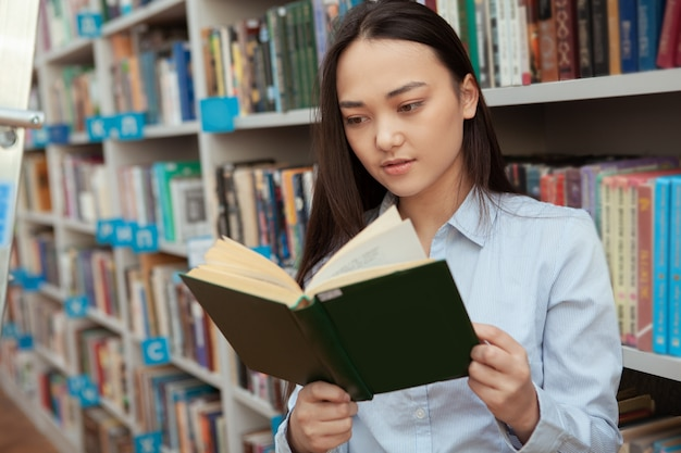 Junge asiatische frau, die ein buch an der bibliothek liest