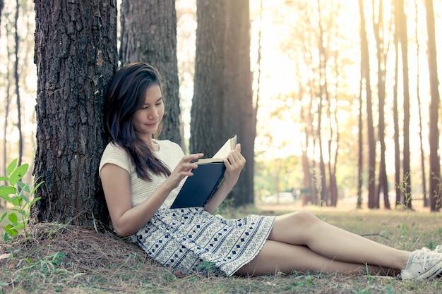 Junge asiatische frau, die ein buch im park im weinlesefarbton liest