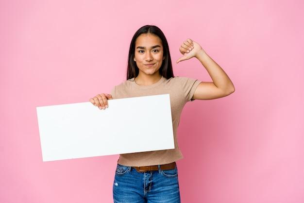Junge asiatische frau, die ein leeres papier für etwas weißes über isolierter wand hält, fühlt sich stolz und selbstbewusst, beispiel zu folgen.