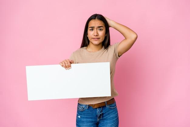 Junge asiatische frau, die ein leeres papier für weißes etwas über isolierter wand hält, die geschockt wird, sie hat sich an wichtiges treffen erinnert.