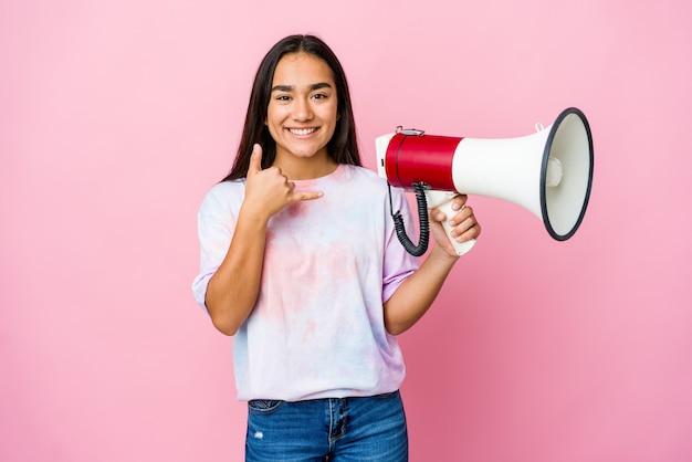 Junge asiatische frau, die ein megaphon lokalisiert auf rosa wand hält, die eine handy-anrufgeste mit fingern zeigt.