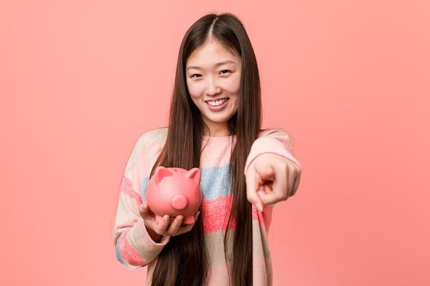 Junge asiatische frau, die ein sparschwein fröhliches lächeln hält, zeigt nach vorne.