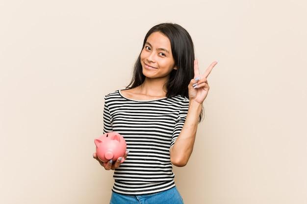 Junge asiatische frau, die ein sparschwein froh und sorglos zeigt ein friedenssymbol mit den fingern hält.