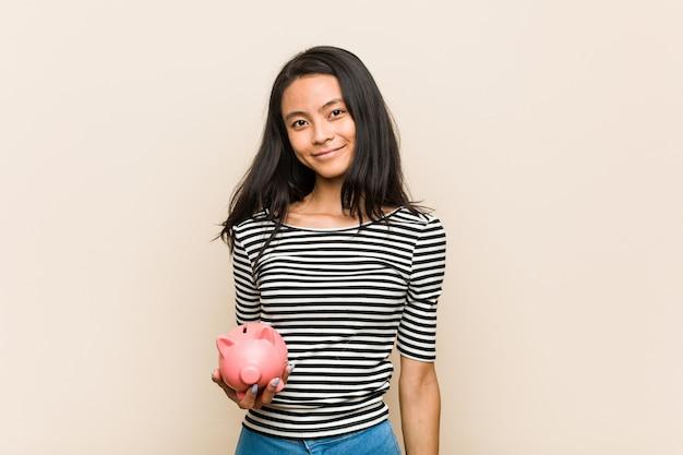 Junge asiatische frau, die ein sparschwein glücklich, lächelnd und nett hält.