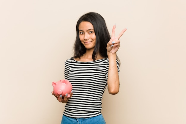 Junge asiatische frau, die ein sparschwein hält, das nummer zwei mit den fingern zeigt.