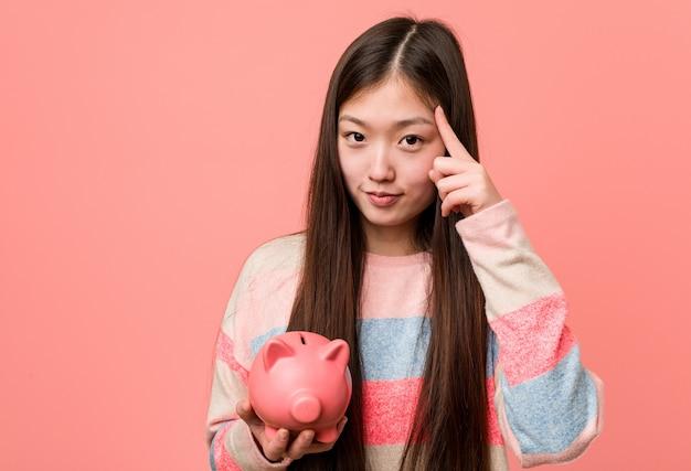 Junge asiatische frau, die ein sparschwein hält, das seine schläfe mit dem finger zeigt und denkt