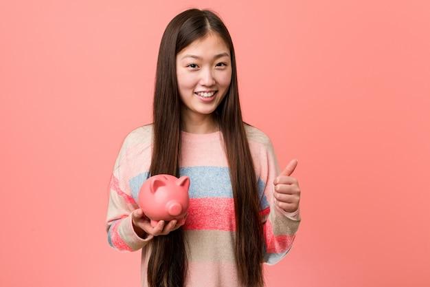 Junge asiatische frau, die ein sparschwein lächelt und daumen hochhält
