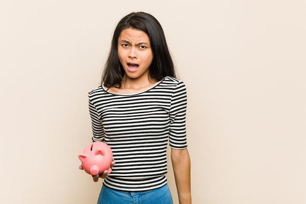 Junge asiatische frau, die ein sparschwein schreit sehr verärgert und aggressiv hält