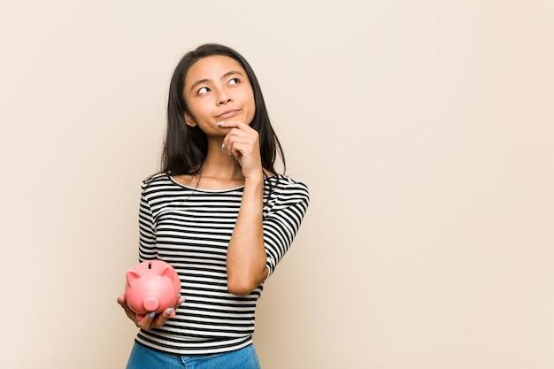 Junge asiatische frau, die ein sparschwein seitlich schaut mit zweifelhaftem und skeptischem ausdruck hält.