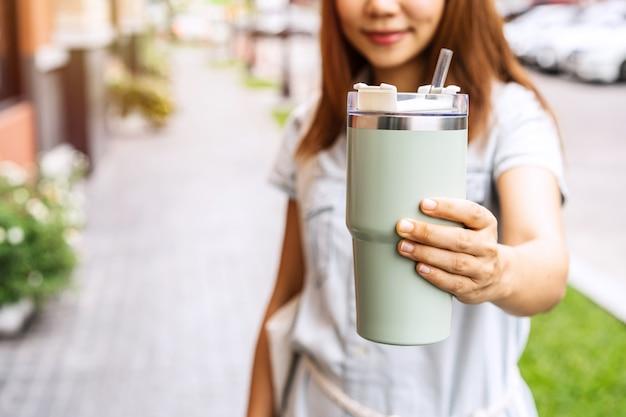 Junge asiatische frau, die ein wiederverwendbares becherglas hält und in der stadt spazieren geht, zero-waste-konzept