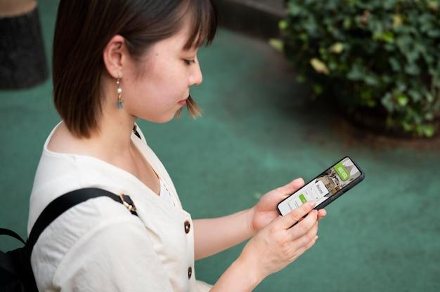 Junge asiatische frau, die eine app auf ihrem telefon betrachtet