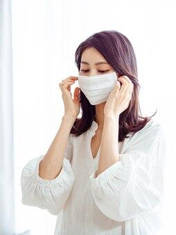 Junge asiatische frau, die eine chirurgische maske trägt, um eine infektion in der häuslichen quarantäne zu verhindern
