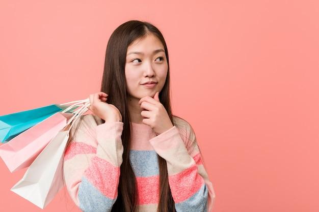 Junge asiatische frau, die eine einkaufstasche seitlich schaut mit zweifelhaftem und skeptischem ausdruck hält.