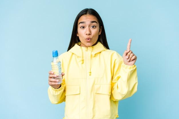 Junge asiatische frau, die eine flasche wasser lokalisiert auf blauem hintergrund hält, der einige große idee, konzept der kreativität hat.