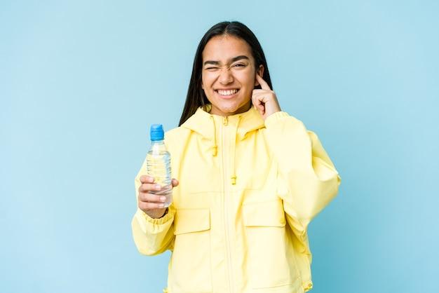 Junge asiatische frau, die eine flasche wasser lokalisiert auf blauer wand hält ohren mit händen bedeckt.