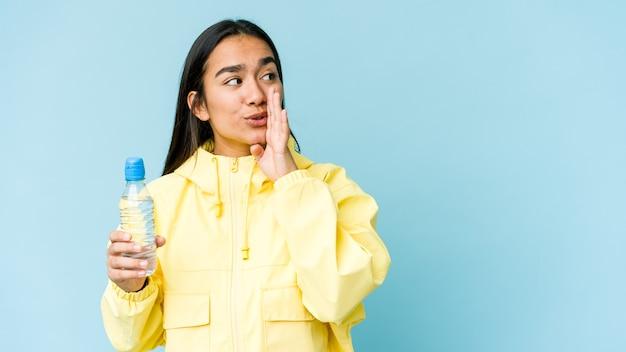 Junge asiatische frau, die eine flasche wasser lokalisiert auf blauer wand hält, sagt eine geheime heiße bremsnachricht und schaut zur seite