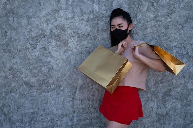 Junge asiatische frau, die eine gesichtsmaske trägt und einkaufstüten am betonwandhintergrund hält