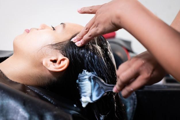 Junge asiatische frau, die eine haarwäsche vom friseur im friseursalon erhält. friseur, der das haar einer jungen frau wäscht. schönheitssalon, haarpflege und lifestyle-konzept der menschen.