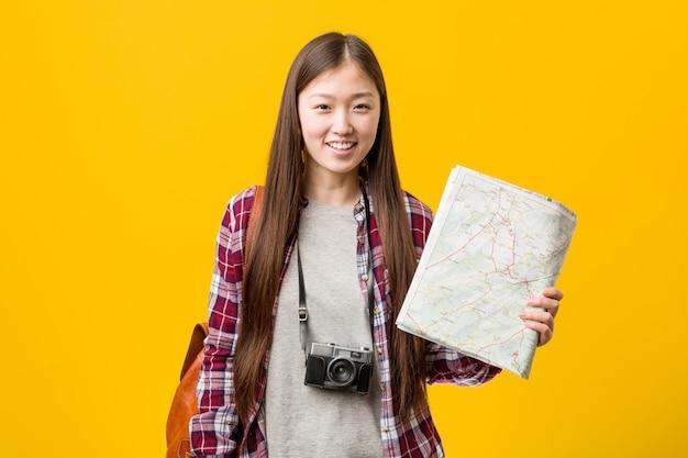 Junge asiatische frau, die eine karte glücklich, lächelnd und nett hält.