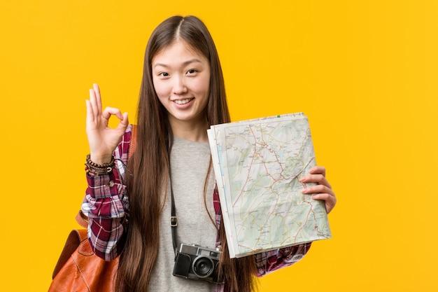 Junge asiatische frau, die eine karte nett und überzeugt hält, okaygeste zeigend.
