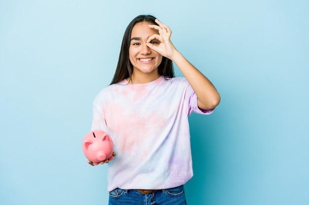 Junge asiatische frau, die eine rosa bank aufgeregt hält, ok geste auf auge halten.