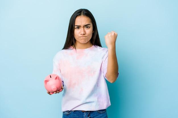 Junge asiatische frau, die eine rosa bank hält, die faust mit aggressivem gesichtsausdruck zeigt.