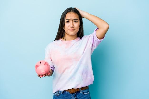 Junge asiatische frau, die eine rosa bank hält, die geschockt wird, sie hat sich an wichtiges treffen erinnert.