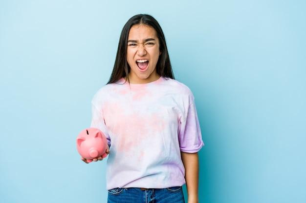 Junge asiatische frau, die eine rosa bank hält, die sehr wütend und aggressiv schreit.