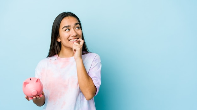 Junge asiatische frau, die eine rosa bank hält, entspannte sich und dachte an etwas, das einen kopienraum betrachtete.