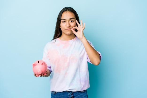 Junge asiatische frau, die eine rosa bank mit den fingern auf den lippen hält, die ein geheimnis halten.