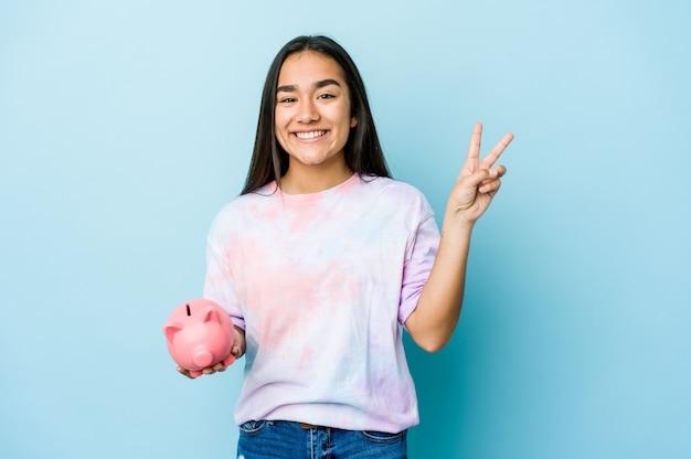 Junge asiatische frau, die eine rosa bank über der isolierten wand freudig und sorglos hält und ein friedenssymbol mit den fingern zeigt.