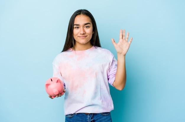 Junge asiatische frau, die eine rosa bank über der isolierten wand hält, die fröhlich zeigt und nummer fünf mit den fingern zeigt.