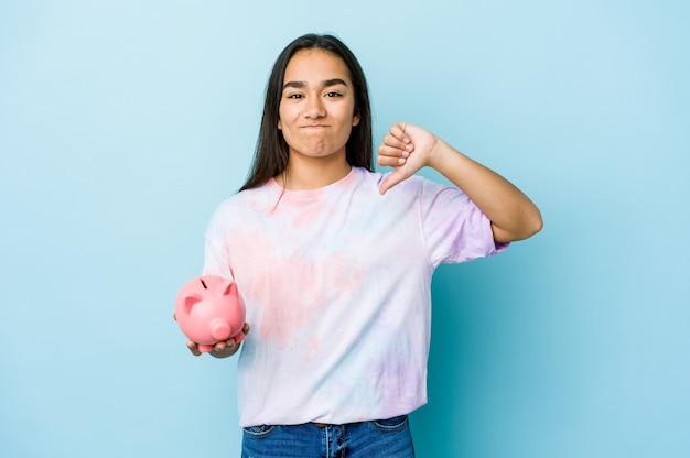 Junge asiatische frau, die eine rosa bank über isolierter wand hält, die eine abneigungsgeste zeigt, daumen nach unten. uneinigkeit konzept.
