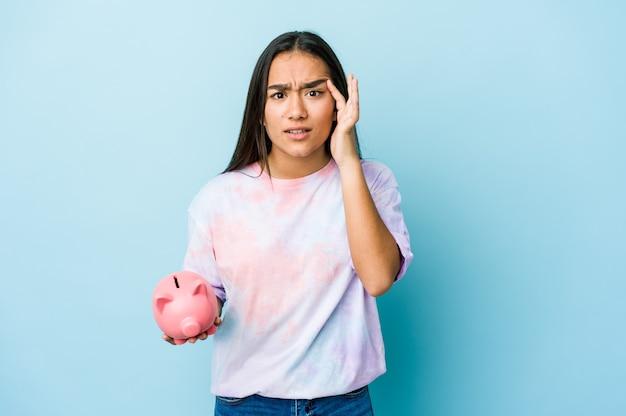 Junge asiatische frau, die eine rosa bank über isolierter wand hält, die eine enttäuschungsgeste mit zeigefinger zeigt.